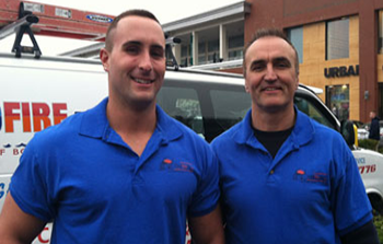 two men in blue polo shirts standing next to each other